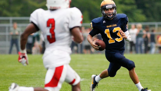 Grand Ledge QB Nolan Bird runs against Sexton's Cody Blaneburg September 9, 2016, at Grand Ledge.  Bird led his Comets to a 40-19 win over Sexton.  [MATTHEW DAE SMITH   for the Lansing State Journal]