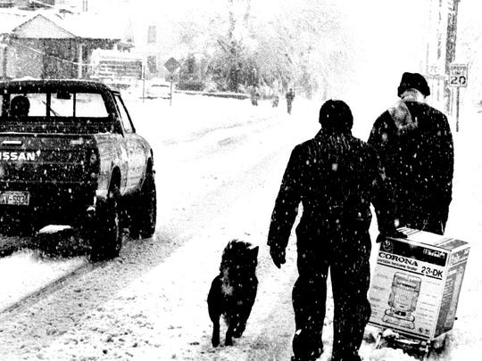 Charlie Jordan, left, and Cliff Wiser use a child's sled to transport a kerosene heater during the Blizzard of '93 on Main Street in Old Fort.