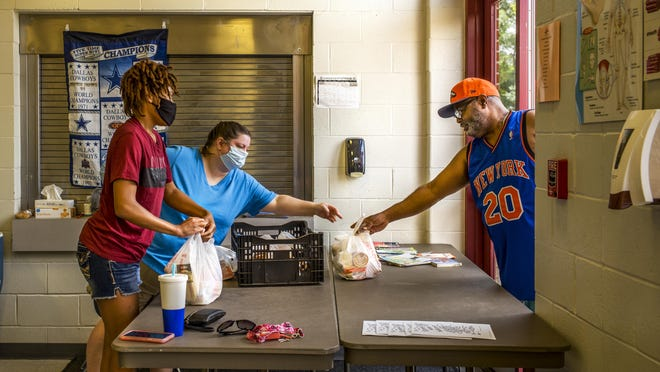 Peoria Public Schools cafeteria worker Tasha Harper, left, and Lincoln Middle School cafeteria manager Gina Stewart pass bags across the table Wednesday, July 1, 2020 to Jeff Harris for his children in the district's summer meal distribution program.