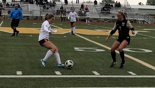 Windsor High School's Brittney Larsen tries to get the ball past Battle Mountain's Avery Weaver during Saturday's Class 4A playoff game in Windsor. The Wizards won 5-0.