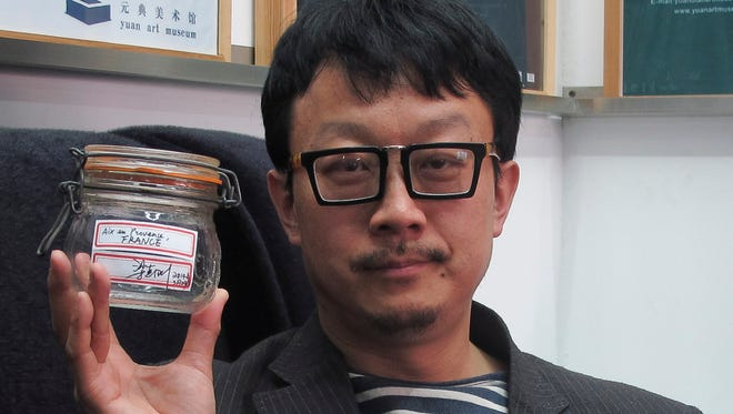 Beijing artist Liang Kegang with the jar of fresh air he collected in Provence, France, in an art gallery in Beijing on April 5, 2014.