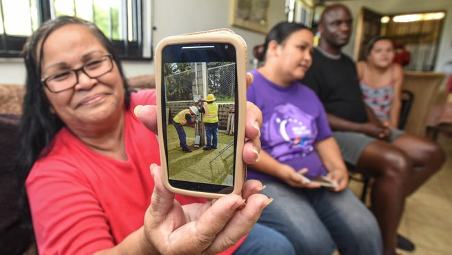 Julie Gumataotao proudly shows off a Nov. 22 image she took of Guam Power Authority employees installing a power meter for her home in Santa Ana, Agat during an interview on Friday, Dec. 2, 2016. Gumataotao acquired the land from the Chamorro Land Trust Commission in 2006 but was unable to get power delivered to the property because she was unable to afford the infrasturcture needed to be installed. But with a donation from The Home Depot, and the Hidden Treasures International missionaries help with the wiring of the home, she and her family can now enjoy the use of island electricity, after over ten years on relying on power provided by a gasoline generator. Also seen are Hidden Treasures missionaries, Melissa Fernandez, right, James Camel and her daughter, Angela Indelacio, seated beside her.