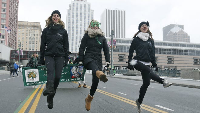 Dancing with the Jamieson Irish Dance & Creative Arts, Katie Jamieson, Megan Rebholz and Caitlyn Brandt jump their way down Main Street during the St. Patrick's Day parade on March 11, 2017.