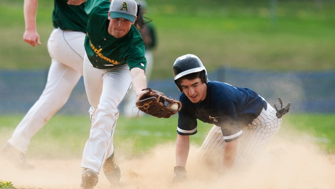 BFA-St. Albans' Kyle Cioffi (4) lunges to catch the ball thrown by the catcher as Burlington's Chris Fenimore (11) slides safely into second base during Saturday's baseball game at Orrie Jay Field.