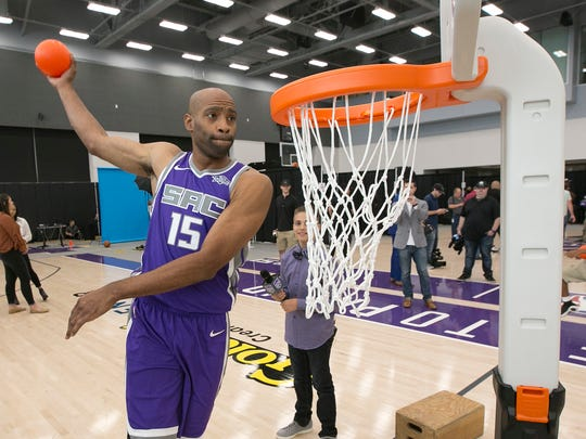 Sacramento Kings guard Vince Carter, a former Slam Dunk Contest champion, demonstrates his dunking ability on a plastic youth basketball hoop.