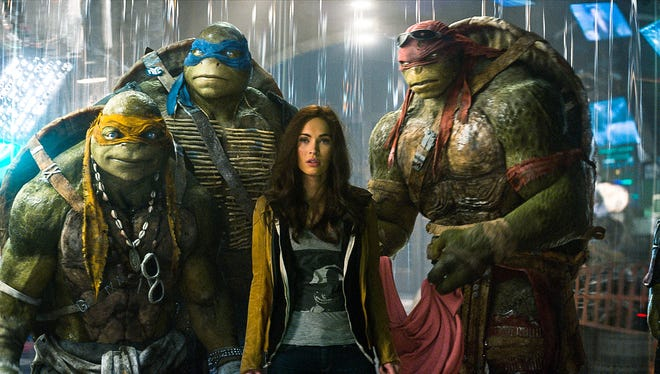 "Michelangelo, Leonardo, Megan Fox as April O'Neil, Raphael, and Donatello in the movie ""Teenage Mutant Ninja Turtles."""