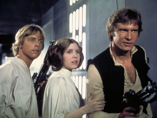 Mark Hamill as Luke Skywalker, Carrie Fisher as Princess Leia and Harrison Ford as Han Solo in the 1977 film 'Star Wars.'