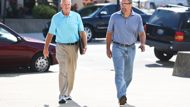 David Camm, right, walks with his uncle Sam Lockhart towards the Floyd County judicial building in New Albany Tuesday morning. Cammis suing Floyd County and the state of Indiana for nearly $30 million for damages relating to the murder trial of his wife and two children, who were killed in 2000. Camm was found not guilty in 2013 after a third trial. Camm spent 13 years in prison for the crimes before a third jury trial found him not guilty. Aug. 12, 2014 By Matt Stone/The C-J