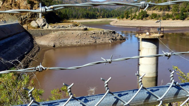 A fence and barbed wire kept the curious away from the dam at Bonito Lake during one of the water draw-down periods to check the structure.