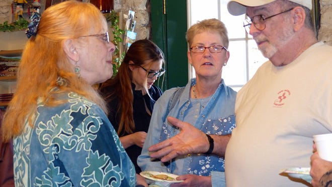 Delana Clements, left, speaks with visitors to The Old Mill during the White Apron Society benefit, where chefs prepared special hor d'oeuvres for guests.