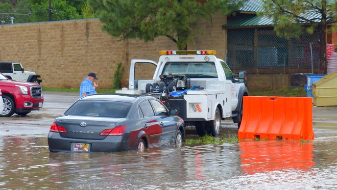 Flooding along Mescalero Trail Friday hid a depression marked by a barricade and a tow truck had to haul out a vehicle.