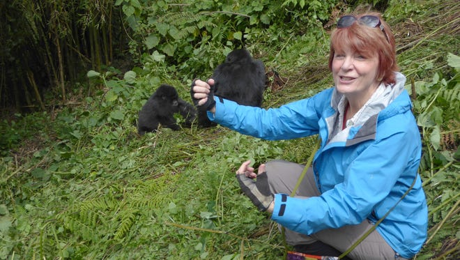 A Rwandan porter snapped this photo of Carolyn Nelson and juvenile gorillas.