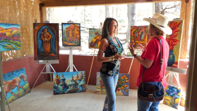 Artist Kathleen Cotton, left, who creates exoctic interpretations on canvas, speaks to one of the art loop tour visitors.