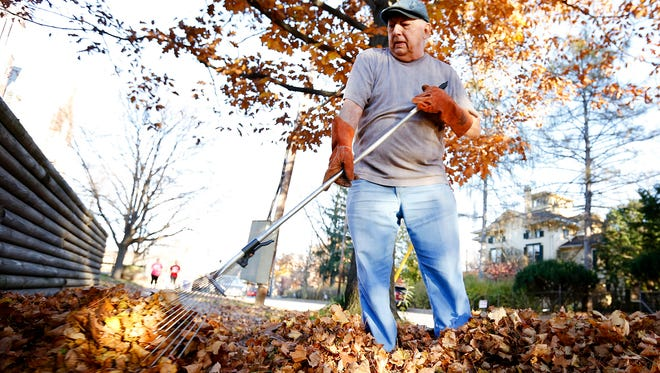 John Saxton rakes the leaves at his West Washington Avenue home to the curb Tuesday. The day was mostly sunny and in the mid-70s in Elmira.