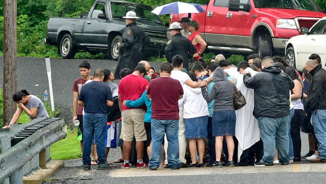 A mix of family members and friends gather to pray while standing on a bridge near the Edenville Community Center on Community Center Road, Monday, July 4, 2016. Early reports are that at 21-year-old man drowned while swimming in a pond in the 9000 block of Mountain Brook Road, St. Thomas.