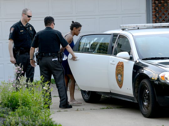A woman is taken into custody and put in the back of a Lansing Township police car Wednesday, June 10, from a house in the Groesbeck neighborhood where more than 75 cats were taken from a house on Autumn Lane. She was later transferred to an East Lansing police car and taken away.