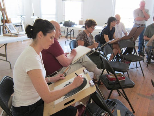 Students sketching during an adult art class at the