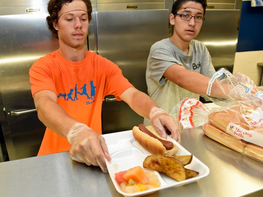Michael King, left, and Carlos Jimenez, both 16, serve meals on Monday, June 27, 2016 at BOPIC summer camp at Chamberburg Area Middle School South.