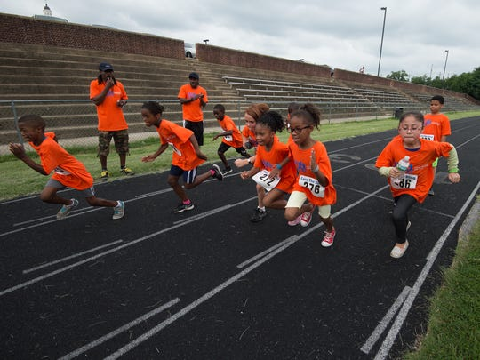 Children run on the track at P.S. DuPont Middle School to complete their final laps of their goal of running 26.2 miles through the program Earn Your Bling, I can do 26.2.