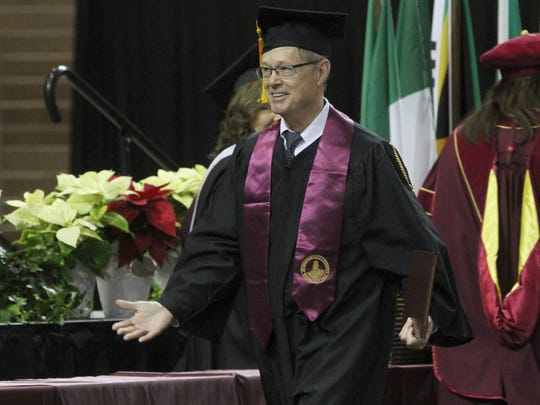 Dr. Robert McBroom Jr. walks across the stage at Midwestern