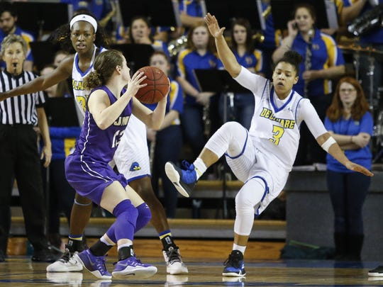 Delaware guard Erika Brown loses her balance after contact with James Madison's Logan Reynolds in the second half of Delaware's 66-51 loss Friday at the Bob Carpenter Center. Delaware forward Nicole Enabosi is at left.