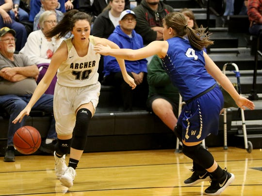 Archer City's Kacey Hasley drives to the basket next to Windthorst's Claire Hemmi Tuesday, Jan. 9, 2018, in Archer City.