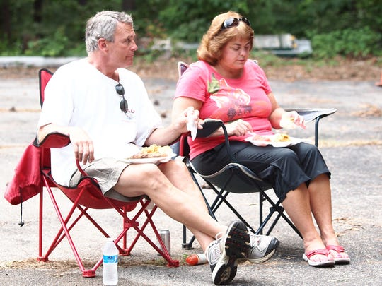 Barry and Jan Matthews eat dinner on the grounds before the outdoor service Sunday evening at Aldersgate United Methodist Church.