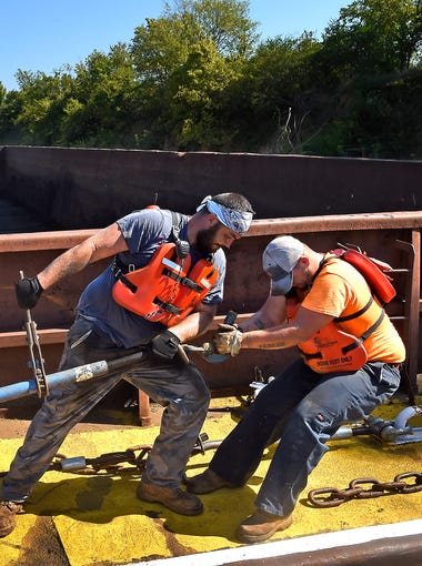 Michael Goff, left, and Jared Henderson work to tie barges together for the trip down the Cumberland River near Nashville.