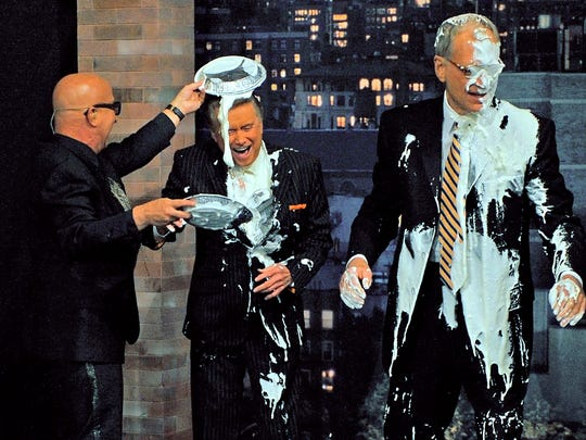 "Paul Shaffer helps David Letterman dole out pies in the face to Regis Philbin as Letterman and Philbin toss pies at each other on ""The Late Show with David Letterman"" in 2009."