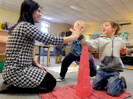 """Katie Dama Jaskolski gives a high-five to two students as they work with the """"pink tower"""" in her Wexford Montessori School kindergarten and preschool classroom Tuesday, March 24. Jaskolski suffers from two rare disorders - Ehlers-Danlos syndrome and postural orthostatic tachycardia syndrome - and founded the Life as a Zebra Foundation to help and support those with hard-to-diagnose diseases."""