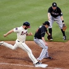 Miami Marlins first baseman Jeff Baker (10) tosses Miami Marlins starting pitcher Nathan Eovaldi (24) a ball getting Atlanta Braves catcher Evan Gattis (24) out at first base in the fifth inning