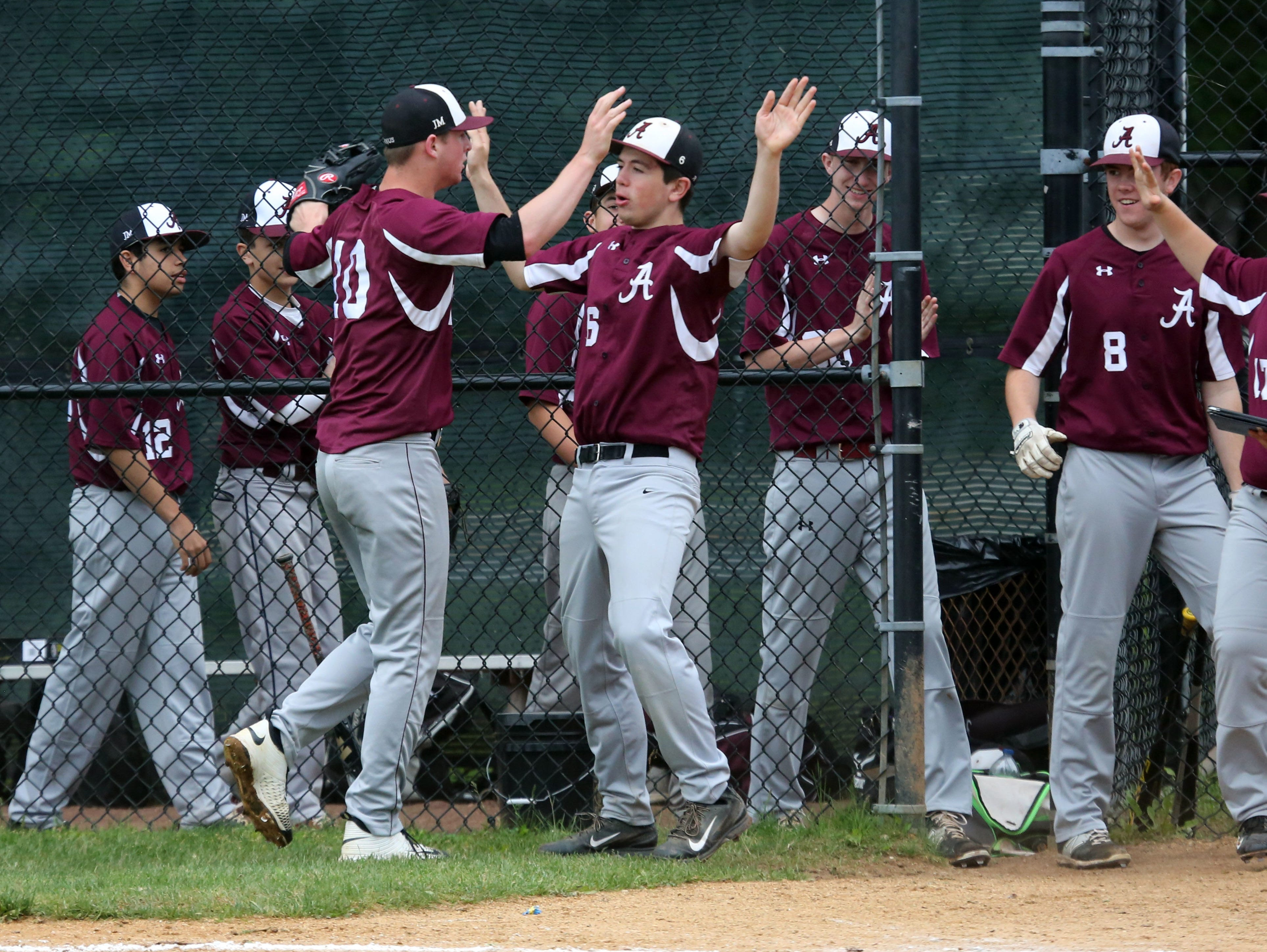 Albertus Magnus pitcher James Reilly is greeted at the dugout by teammates during their Class B game against Ardsley at Ardsley High School, May 21, 2016.