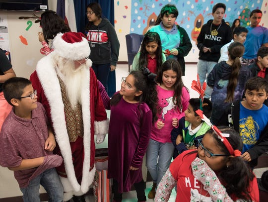 Students gather around Santa Claus during Crockett Elementary's second annual Christmas Tree Angel event on Wednesday, Dec. 13, 2017.