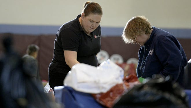 Salvation Army Capt. Amy Portillo, left, and Lucinda Semsick sort gifts as volunteers and staff at the Lebanon Salvation Army where busy preparing for the annual Angel Tree Christmas gift distribution in this photo taken on Dec. 15, 2014. More than three dozen businesses, organizations, and churches, along with countless individuals donated toys, clothing, winter coats and other apparel that were distributed to the children of 365 local needy families who registered for the program.