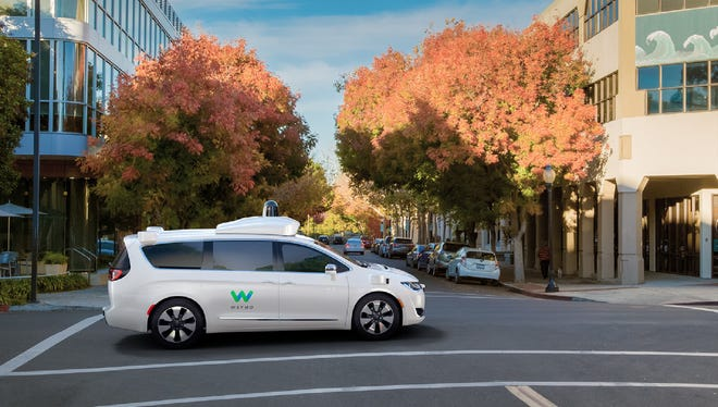 A Chrysler Pacifica minivan cruises down the street packed with self-driving car technology produced by Waymo, the new name for Google's self-driving car program.