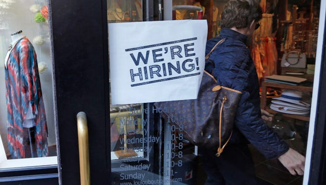 "A woman passes a ""We're Hiring!"" sign in this file photo of a clothing store in Boston. Employers posted more open positions in January compared with December and the number of Americans quitting jumped."