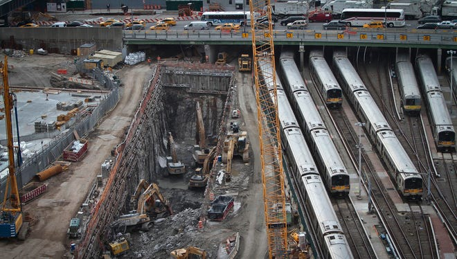 In this April 17, 2014, file photo, backhoes excavate in a hole reserved for a rail tunnel, left, during the early days of construction at the Hudson Yards redevelopment site on Manhattan's west side in New York. A concrete box was planned inside the project to preserve space for a tunnel from Newark to New York City that would allow it to double rail capacity across the Hudson River. An environmental study has been released for the Hudson River rail tunnel project, amid concerns the effort could lose key federal funding under President Donald Trump's proposed budget.