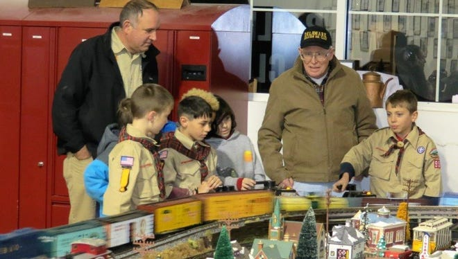 A visiting Scout tries out the controls of a model train display at the club as club members and fellow Scouts look on.