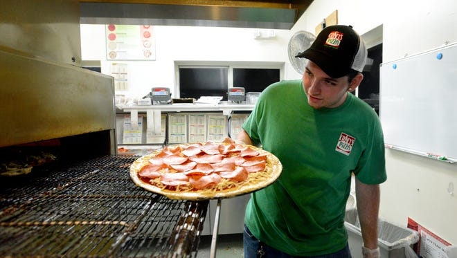 Tyi Coykendall puts a pizza in the oven Saturday night, May 12, 2018, at Cristy's Pizza in Amanda. Coykendall will graduate from Amanda-Clearcreek High School after making up nearly all of his school work in just two years.