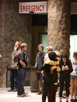 Students embrace outside a hospital emergency room in Flagstaff, Ariz., on Friday, Oct. 9, 2015, after an early morning fight between two groups of college students escalated into gunfire, leaving one person dead and three others wounded, authorities said. The shooting occurred outside a dormitory near the Northern Arizona University campus.