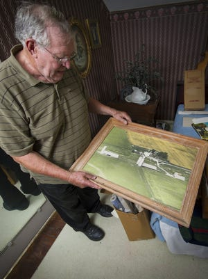 Richard Himsel hold an aerial photograph of his Danville farm taken about 20 years ago. Himsel, 74, has lived his whole life on or near the farm his family has owned since 1940.