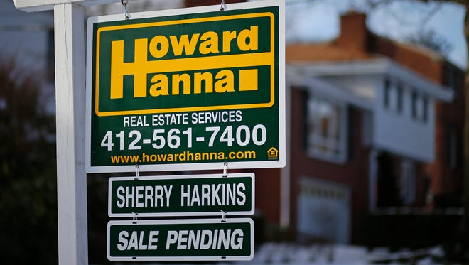 In this  Thursday, Jan. 9, 2014, photo, a for sale sign with a sale pending hangs in front of a house in Mount Lebanon, Pa.