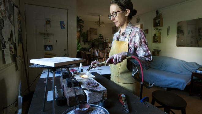 Jeri Bartley uses a torch to fuse silver to copper as she makes a piece of jewelry at her home Wednesday. Bartley has been making metal art jewelry for about 7 years and plans to expand her skills to blacksmithing.