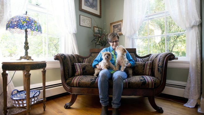 Nancy Merrill sits with her Australian Silky Terriers, Maggie and Lila, in the parlor area of Applewood Manor Inn bed-and-breakfast which she owns with her husband, Larry. The house has six guest rooms including a luxury cottage, seven fireplaces, a parlor area with a piano and a living room and dining area for socializing. Guests at the inn are treated to a three-course breakfast and a social hour every day.