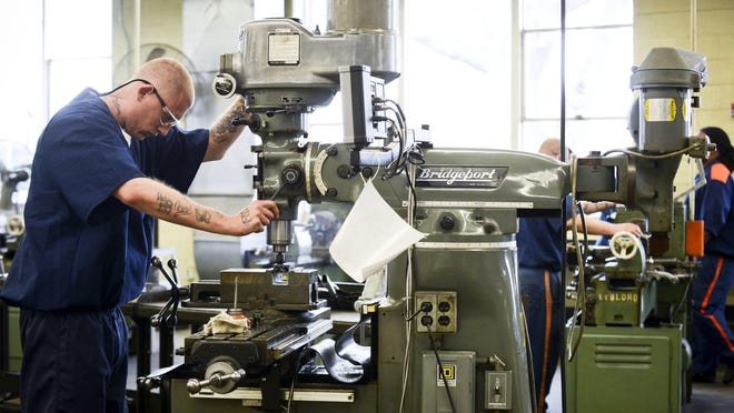 In this photo taken Monday, April 15, 2016, onmate Samuel Sullivan operates a machine in the CNC and Machine Tool shop as part of the Vocational Village program at the Richard A. Handlon Correctional Facility in Ionia, Mich. The vocational program enrolls eligible prisoners in career-worthy technical education such as welding, carpentry and automotive technology. Inmates are housed together to foster a supportive, learning environment. (Emily Rose Bennett/The Grand Rapids Press via AP) ALL LOCAL TELEVISION OUT; LOCAL TELEVISION INTERNET OUT; MANDATORY CREDIT