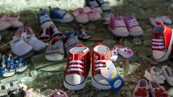 Rows of baby shoes were set out by Military Accountability and Transparency Alliance members at a memorial they created for babies lost to miscarriages at the entrance of the abandoned George Air Force Base hospital on Sunday July 12, 2020. The group filed an administrative claim on June 30 against the federal government, which serves as notification of their intent to sue.