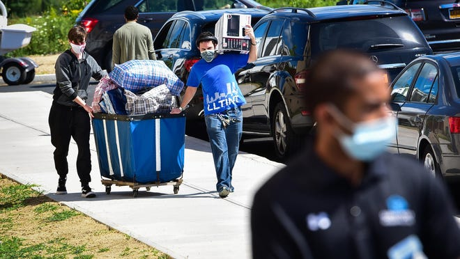 Will Logatto, right center, carries a microwave over his shoulder while helping his brother Enzo Logatto move into college housing Thursday, Aug. 20, 2020, at SUNY Polytechnic Institute in Marcy. All classes for the college begin Monday.