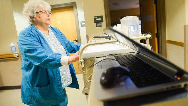 Sharon Margot, an LPN of the Sitrin Health Care Center in New Hartford, pushes a cart down a hallway while working on Friday, Jan. 12, 2018. Margot works in one of the long term care houses. Their nursing home is a group of houses that function more like a home with a small number of residents.