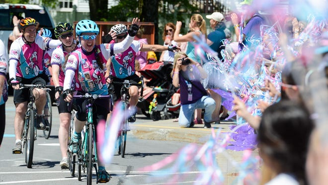 Cyclists participating in the Ride for Missing Children wave to Hart's Hill Elementary School students as they make a visit during last year's event.