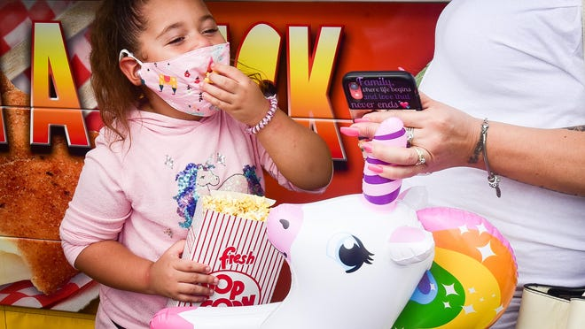 Utica resident Jarieys Colon playfully attempts to eat popcorn with a mask while checking out Carnival Eats Utica with her grandmother Saturday at Notre Dame Elementary School.